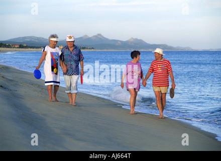 Ältere Menschen im Ruhestand Paare zu Fuß am Sandstrand von San Jose del Cabo in Mexiko - Stockfoto