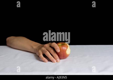 Arm ruht auf Tisch und hält Apfel - Stockfoto