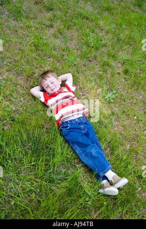 Kleiner Junge auf dem Rasen liegend mit geschlossenen Augen und die Hände hinter den Kopf - Stockfoto