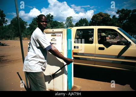 Ein junger schwarzer afrikanischer Mann mit einer Hand betriebenen Zapfsäule tanken einen Mietwagen in Malawi - Stockfoto