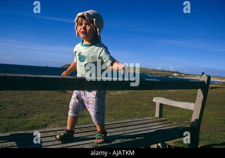 Eine kleine Mädchen selbstbewusst geht und balanciert auf einer Bank am Meer während des Urlaubs in Dorset, England - Stockfoto