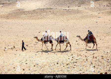 Drei Kamele zu Fuß mit Touristen und Reiseführer auf steinigen Wüste in der Nähe der Pyramiden Gizeh-Cairo-Ägypten - Stockfoto