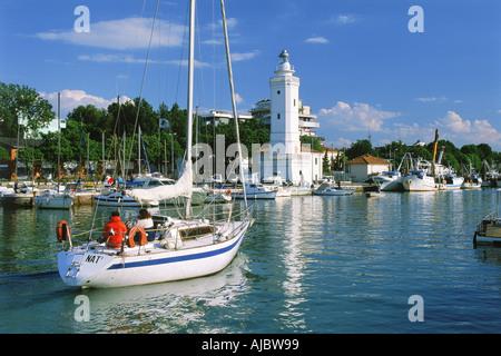 Boote und Leuchtturm am Hafen Rimini oder Emilia Romagna im Adriatischen Meer auf italienische Riviera - Stockfoto