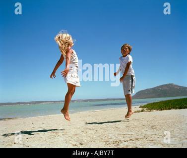 Jungen und Mädchen am Strand, springen - Stockfoto