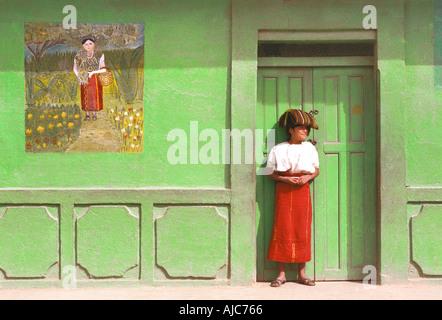 Ixil Maya-Frau stand in der Tür ihrer Heimat Nebaj El Quiche Guatemala der rote Rock ist ein Symbol der Ethnizität - Stockfoto