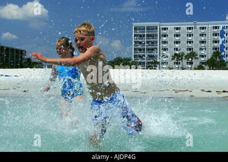 zwei Kinder spielen am Strand läuft in das Meer und Wasser plantschen - Stockfoto