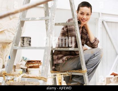 Raumausstatter bei der arbeit  Malerin Dekorateur sitzt auf einer Bierkiste eine Pause und ...