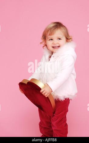 Zwei Jahre altes Mädchen mit rotem Samt überzogen Valentinstag Herz - Stockfoto