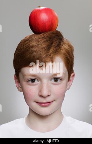 Junge, einen Apfel auf dem Kopf balancieren - Stockfoto