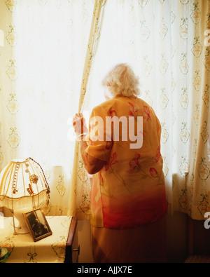 Ältere Frau aussehende Öffnung Vorhang - Stockfoto