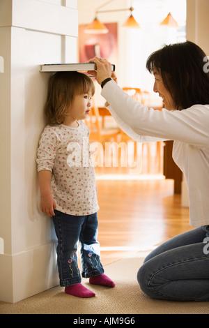 Measing asiatische Mutter ihre kleine Tochter Höhe gegen eine Tür zu Hause - Stockfoto