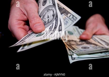 Ein Mann übergibt fünfzig-Dollar-Scheine aus einem großen Bündel von Bargeldgetreide schließen der Hände vor schwarzem - Stockfoto