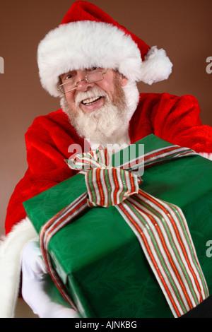 Santa Claus hält ein Geschenk - Stockfoto