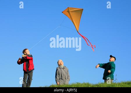 Großeltern und ihre Enkel sind einen Drachen zusammen fliegen. - Stockfoto