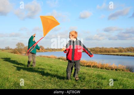 ein Großvater und sein Enkel fliegen einen Drachen zusammen - Stockfoto
