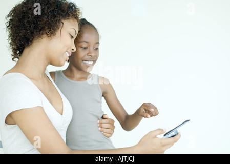 Mutter und Tochter zusammen mit Blick auf Handy, Lächeln - Stockfoto