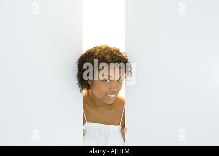 Junge Frau spähen durch Öffnung in Wänden, lächelnd in die Kamera, Porträt Stockfoto