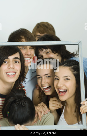 Junge Freunde Rahmen zusammenhalten, lächelnd in die Kamera - Stockfoto