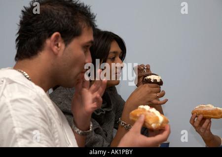 zwei asiatische Studenten essen Kuchen und Muffins in einem Café mit Freunden - Stockfoto