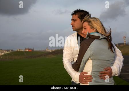 junges Paar stehen umfassende Blick über Felder - Stockfoto