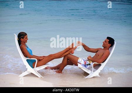 Malediven. Junges Paar in Badehosen sitzen auf Liegen im flachen Wasser. - Stockfoto