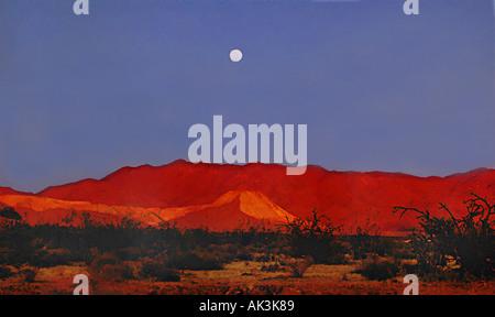 Ein Vollmond steigt über Chlorid Arizona USA, während die untergehende Sonne immer noch auf das Wüste Land scheint - Stockfoto