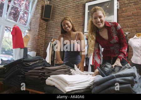 Junge Frauen auf der Suche durch Hose in einem Bekleidungsgeschäft - Stockfoto