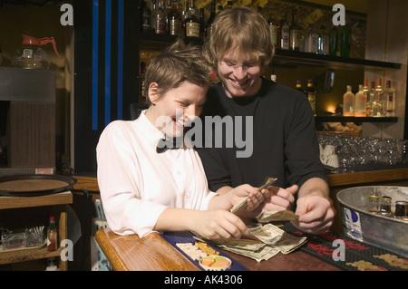 Zwei Restaurant-Arbeiter zählen Bargeld auf der Leiste oben - Stockfoto