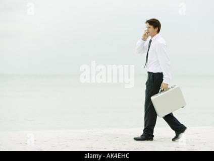 Geschäftsmann mit Handy und Aktenkoffer am Strand tragen - Stockfoto