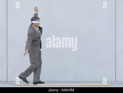 Mit verbundenen Augen Geschäftsmann zu Fuß auf Holzbrett - Stockfoto