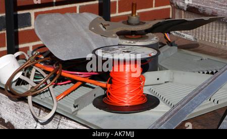 Eine Rolle von leuchtend roten electical Draht gegen einen Haufen Bauschutt. - Stockfoto