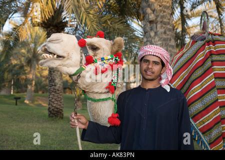Arabische Kultur, lächelnden Jungen arabischen Kamel Fahrer dekoriert mit arabischen Kamel in der Außenanlage, VAE, - Stockfoto