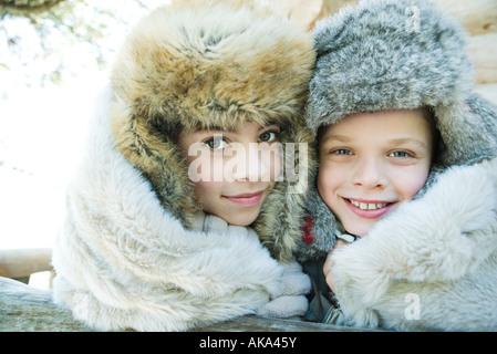 Bruder und Schwester lächelnd in die Kamera, Wange an Wange, beide tragen Pelz Mützen, Porträt - Stockfoto