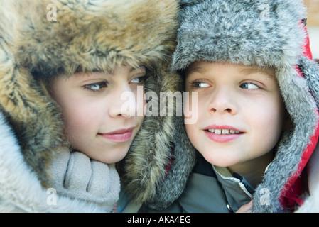 Schwester und Bruder tragen Pelz Mützen, Lächeln einander, Porträt - Stockfoto