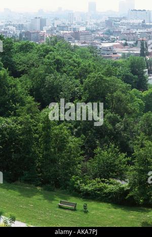 Parkbank im grünen Park, Stadt im Hintergrund - Stockfoto