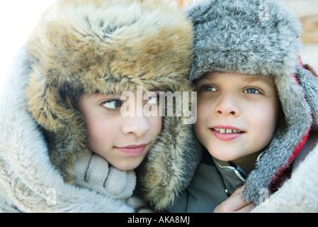 Schwester und Bruder tragen Pelz Mützen, Lächeln, wegschauen, Porträt - Stockfoto