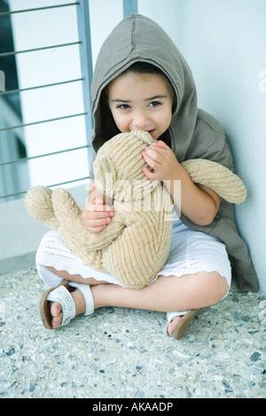 Kleines Mädchen sitzt am Boden, Flüstern ins Ohr Teddy Bär, in voller Länge - Stockfoto