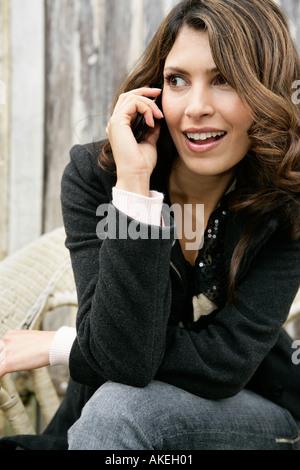 Frau sitzt im freien reden über Handy - Stockfoto