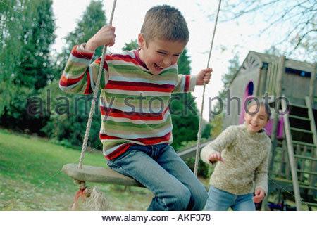 Kinder spielen auf einer Schaukel - Stockfoto