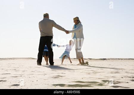 Großeltern mit Enkeln am Strand tanzen - Stockfoto