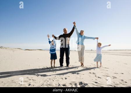 Großeltern mit Enkeln spielen am Strand - Stockfoto