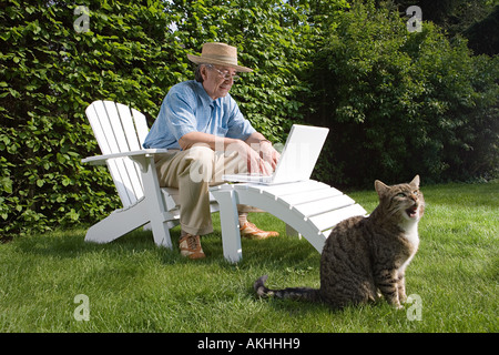 Mann im Garten mit Laptop und Katze - Stockfoto
