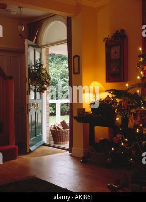 Offene haustür  Kranz auf offene Haustür mit Blick auf hohen Weihnachtsbaum und ...