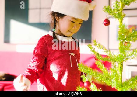 Kleines Mädchen mit Weihnachtsbaum - Stockfoto