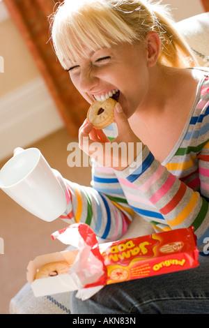 Frau essen Kekse mit Getränk - Stockfoto
