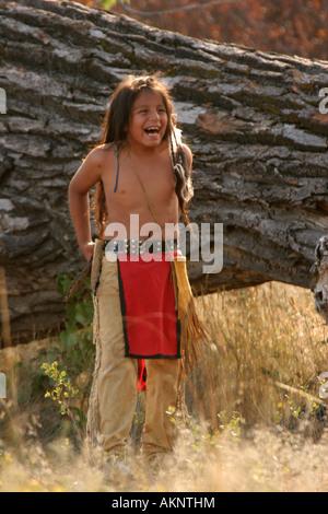 Ein junger Indianer Sioux Indianer junge Lachen draußen durch einen großen umgestürzten Baum - Stockfoto