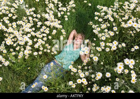 Eine junge Frau auf dem Rasen liegend - Stockfoto