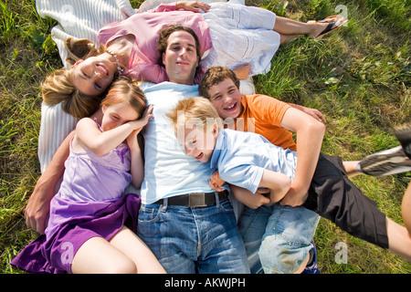 Junge Familie liegen im Feld, umarmen, erhöht, Ansicht - Stockfoto