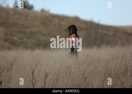 Ein Native American Indian junge läuft in die getrocknete Gräser - Stockfoto