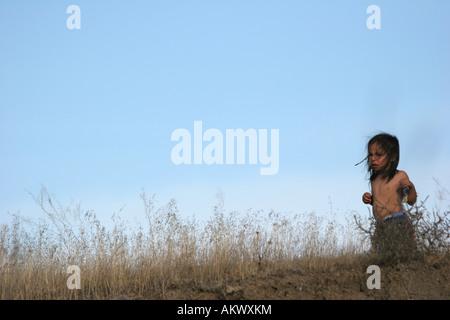 Ein Native American Indian junge läuft in verärgert die getrocknete Gräser, die auf der Suche - Stockfoto